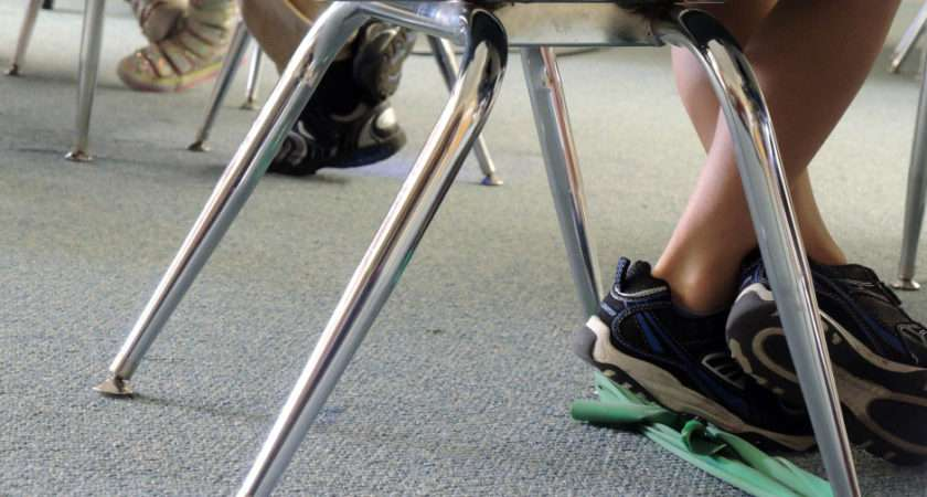 Green Rubber Band Stretched Between Legs His Classroom Chair